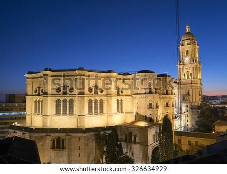 Malaga cathedral illuminated at dusk - stock photo
