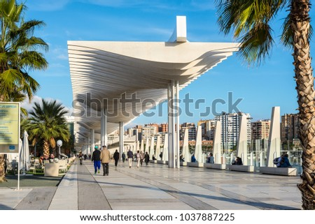 Malaga, Spain - December 7, 2016: People are walking along the embankment (Paseo Del Muelle Dos Promenade) which stretches through port under a construction resembeling white wave in Malaga, Spain.