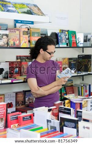 MALAGA, SPAIN - JUNE 11: Unidentified person reads a book during the 2011 Malaga Book Fair on June 11, 2011 in Malaga, Spain - stock photo