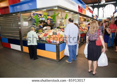 MALAGA, SPAIN - JUNE 10: Unidentified sellers pack fruits at their shop in the popular central market on June 10, 2011 in Malaga, Spain.  It was renovated in 2010 and it was reopened on March 2011. - stock photo