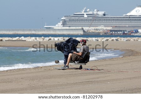 MALAGA, SPAIN - MAY 28: An unidentified cameraman broadcasts an air show at Malagueta Beach at Spanish Armed Forces Day on May 28, 2011 in Malaga, Spain. - stock photo
