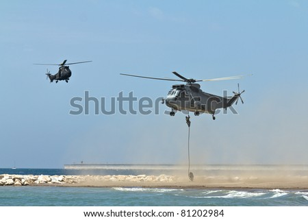 MALAGA, SPAIN - MAY 28: Unidentified soldiers descend from a Sea King helicopter of the Spanish Navy at Malagueta Beach during the Spanish Armed Forces Day on May 28, 2011 in Malaga, Spain.