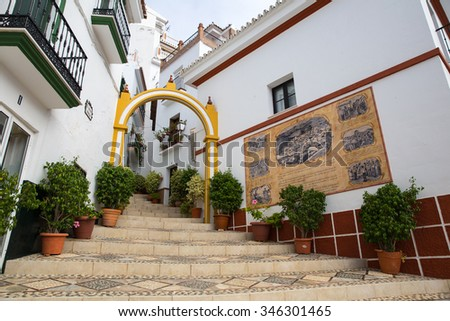 MALAGA, SPAIN - OCTOBER 28, 2015: Picturesque street of Almogia shows in a wall some historic data and habits of the village. Text written in spanish. - stock photo