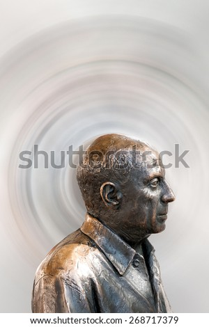 Malaga, Spain - September 30th, 2014: Metal bust of the famous painter Pablo Picasso in front of a radially blurred background as a symbol of the painters charisma and imagination