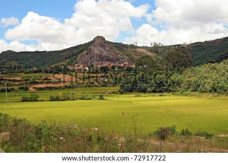 Malagasy Countryside: landscape (Madagascar) with small village at foot of rock mountain and rice fields in foreground. - stock photo