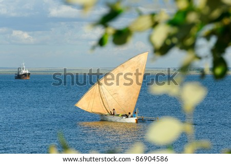 Malagasy fishermen and their little dhow - stock photo