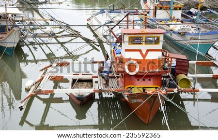 Malandog,Panay island, Philippines - December 4,2014: Fishermen putting outriggers out in the river to protect the boats from Super Typhoon Hagupit (Ruby) - stock photo