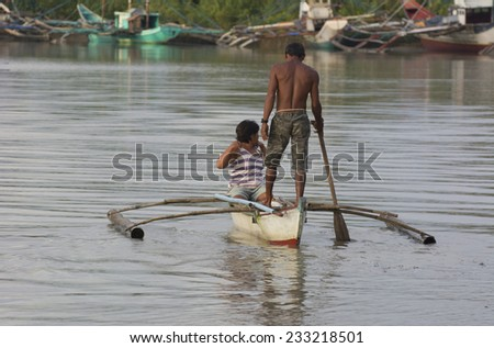 Malandog, Philippines - October 20, 2014: A copuple in an traditional Filipino outrigger going out to fish during the sunset - stock photo