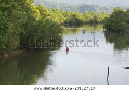 Malandog, Philippines - October 16, 2014: Man looking for food in a slow moving river  - stock photo