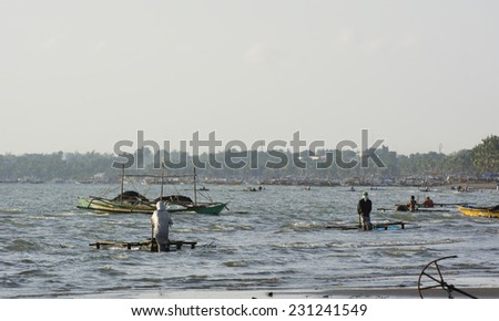 Malandog, Philippines - October 22, 2014: People catching Milkfish fry (bangus) to sell to the milkfish farms in the province of Antique - stock photo
