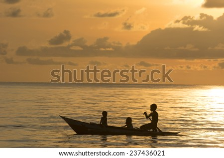 Malandog, Philippines - October 20, 2014: Three small children driving an outrigger in Philippines during a colorful sunset at the island of Panay in central visayas in the Philippines - stock photo