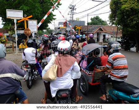 MALANG, INDONESIA - OCTOBER 1, 2016: Motorcyclists at a Railroad crossing, Malang, Indonesia.