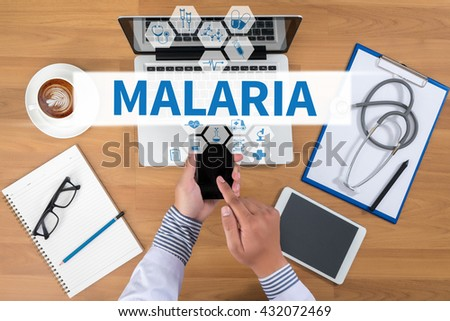 MALARIA Doctor working at office desk and using a mobile touch screen phone, computer and medical equipment all around, top view, coffee - stock photo