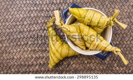 Malay dish ketupat daun palas or rice dumpling where glutinous rice is wrapped in a triangular shape using the leaves of the fan palm  - stock photo