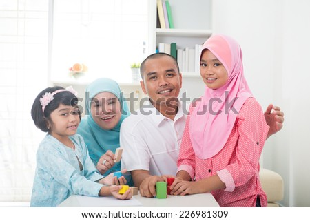 Malay family at home. Muslim girl building a wooden toy house. Southeast Asian parents and child living lifestyle.  - stock photo