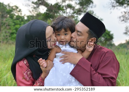 malay family having fun in the park ,malaysian people. Mother and father kissing his daughter. - stock photo