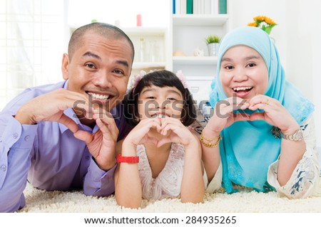 Malay family making love shape with hands - stock photo