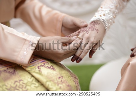 malay wedding groom bolstering gold ring on bride's finger - stock photo