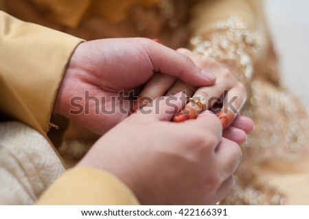 malay wedding groom bolstering gold ring on bride's finger