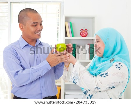 Malay woman giving an apple to her husband. Healthy eating concept.