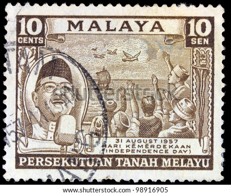 MALAYA - CIRCA 1957: A stamp printed in Malaya shows people cheering for Independence Day, circa 1957 - stock photo