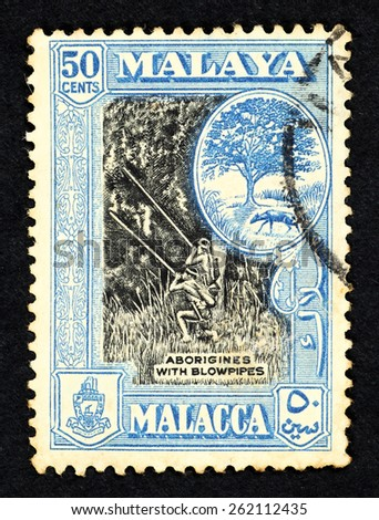 MALAYA - CIRCA 1957: Blue color postage stamp printed in Malacca (Federation of Malaya) with illustrative image of aborigines with blowpipes and the symbol of Malacca national, animal the mousedeer. - stock photo