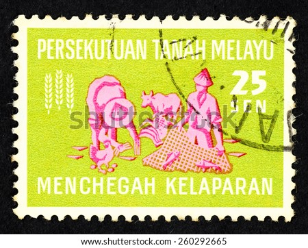MALAYA - CIRCA 1963: Green color postage stamp printed in Federation of Malaya with illustrative image of farmer and fisherman to commemorate hunger prevention. - stock photo