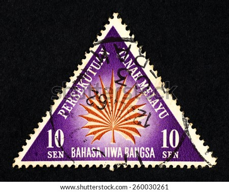 MALAYA - CIRCA 1962: Purple color triangle shaped postage stamp printed in Federation of Malaya with illustrative image of a leaf.  - stock photo