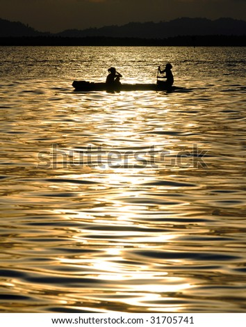 Malaysia Borneo Region of Sabah Mabul island Fisherman travel with traditional boat in silhouette during sunset - stock photo