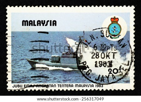 MALAYSIA - CIRCA 1983: Blue color postage stamp printed in Malaysia with image of a military navy frigate at sea, to commemorate the golden jubilee of the Malaysian Armed Force. - stock photo