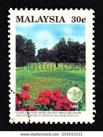 MALAYSIA - CIRCA 1993: Postage stamp printed in Malaysia with image of a golfer on the green of a golf club to commemorate the 100th Anniversary of the Royal Selangor Golf Club. - stock photo