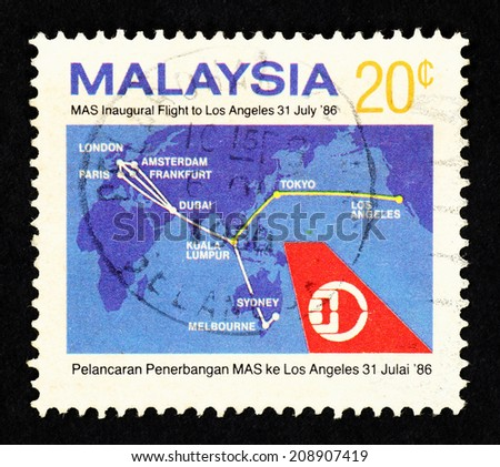 MALAYSIA - CIRCA 1986: Postage stamp printed in Malaysia with image of Malaysia Airlines emblem against a global map to commemorate MAS inaugural flight from Kuala Lumpur to Los Angeles. - stock photo