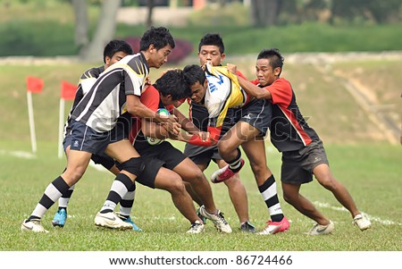 MALAYSIA - OCTOBER 15: Unidentified participants in action during a 10 Side Rugby Tournament Vice-Chancellor Cup at National Defense University Of Malaysia, Kuala Lumpur, Malaysia on October 15, 2011. - stock photo