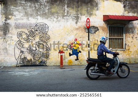 MALAYSIA, PENANG, GEORGETOWN - CIRCA JUL 2014: Man on a motorcycle, passing two diverse murals painted on the same wall. - stock photo