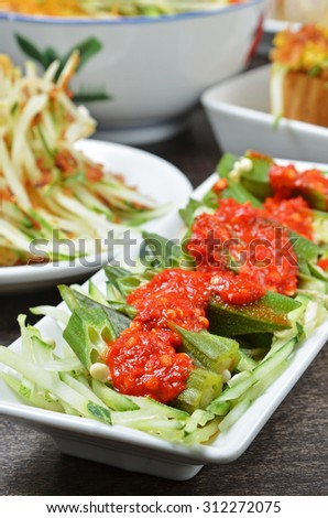 Malaysian cuisine - Okra with spicy sauce on white plate