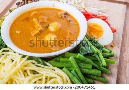 Malaysian curry noodles ingredients with a bowl of curry gravy, yellow noodle, vegetable, bean sprout, calamansi, chili, hard boiled egg and cockle meat on wooden board. - stock photo