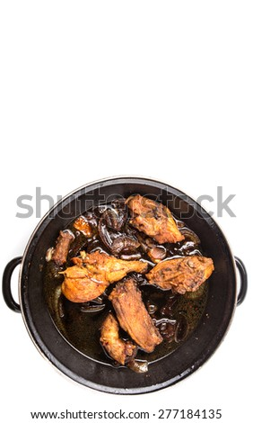 Malaysian dish of deep fried chicken in with black soy gravy in a saute pan