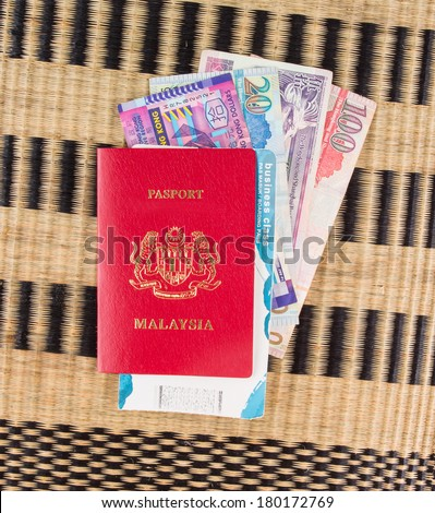 Malaysian passport with Hong Kong currency and airplane boarding pass on a wicker mat - stock photo