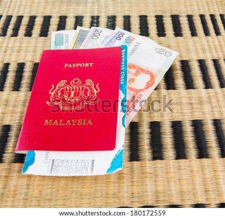 Malaysian passport with Philippine currency and airplane boarding pass on a wicker mat - stock photo