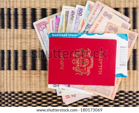 Malaysian passport with various currency and airplane boarding pass on a wicker mat - stock photo
