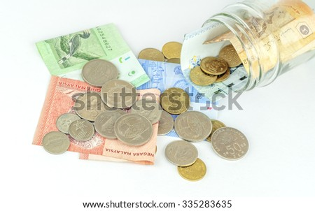 Malaysian Ringgit coins and Notes spilling out of glass bottle.
