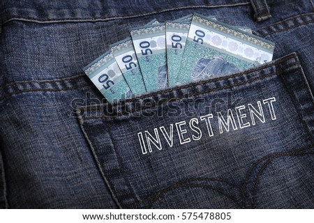 Malaysian ringgit notes sticking out of the blue jeans pocket with word INVESTMENT. Business and finance concepts.