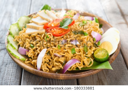 Malaysian style maggi goreng mamak  or spicy fried curry instant noodles.  Asian cuisine, ready to serve on wooden dining table setting. Fresh hot with steamed smoke. - stock photo