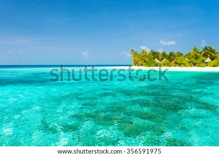 Maldives. Island in the ocean. Palm trees on the white sand beach. Turquoise water of the lagoon. Roof bungalow suite.  - stock photo