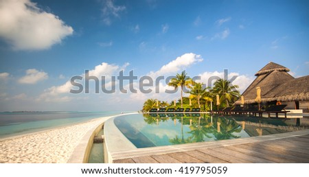 Maldives, Kuredu and lovely morning view of a swimming pool, beach and palm trees. - stock photo