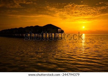 Maldives sunset with water villas silhouette and cloudy sky