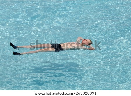 Maldives.  Teenager has a rest on turquoise transparent water of ocean  - stock photo