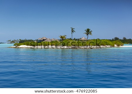 Maldives. Tropical island with palm trees. Water villas resort. Beautiful ocean and clear blue sky. Travel background. Vacation wallpaper.