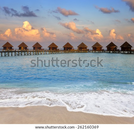 Maldives.  Villa on piles on water at the time sunset