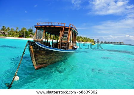 Maldivian dhoni in front of the turquoise bay and island - stock photo
